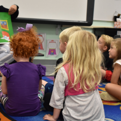 Picture of students listening to a teacher read Goodnight Moon.